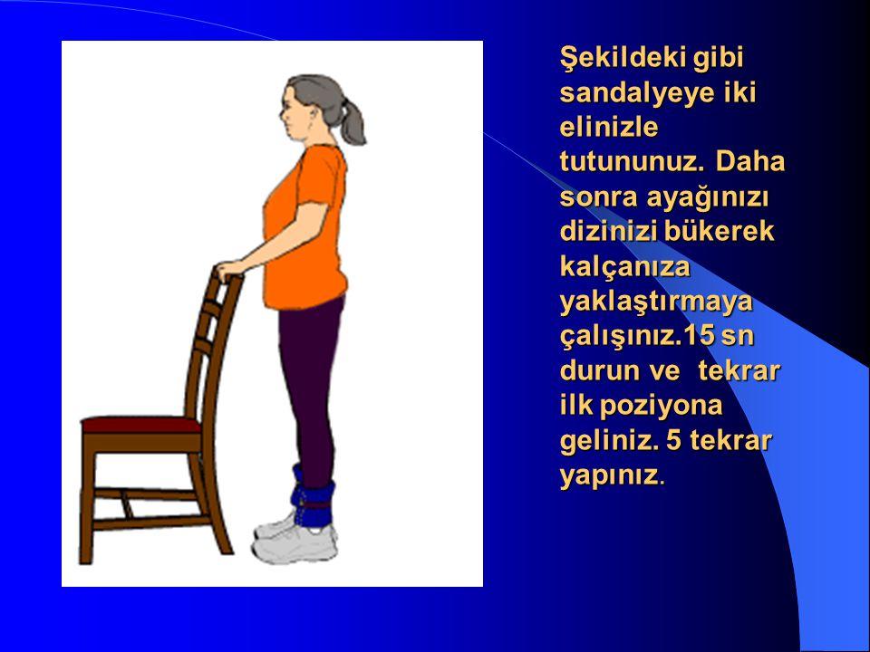 Şekildeki gibi sandalyeye iki elinizle tutununuz. Daha sonra ayağınızı dizinizi bükerek kalçanıza yaklaştırmaya çalışınız.15 sn durun ve tekrar ilk po