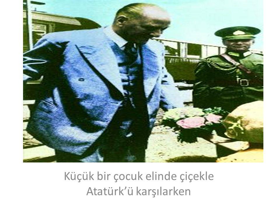 Küçük bir çocuk elinde çiçekle Atatürk'ü karşılarken