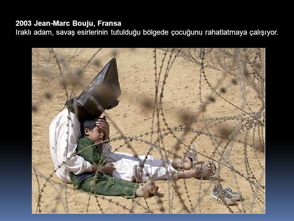 2003 Jean-Marc Bouju, Fransa Iraklı adam, savaş esirlerinin tutulduğu bölgede çocuğunu rahatlatmaya çalışıyor.