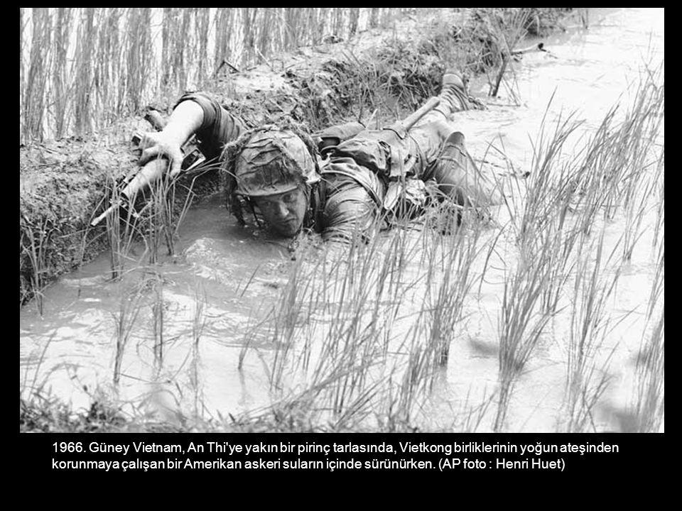 1966. Güney Vietnam, An Thi'ye yakın bir pirinç tarlasında, Vietkong birliklerinin yoğun ateşinden korunmaya çalışan bir Amerikan askeri suların içind