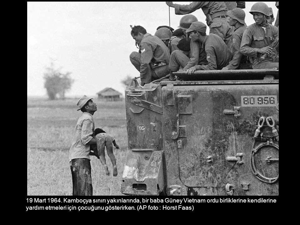 19 Mart 1964. Kamboçya sınırı yakınlarında, bir baba Güney Vietnam ordu birliklerine kendilerine yardım etmeleri için çocuğunu gösterirken. (AP foto :
