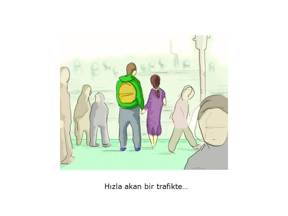 …karşıdan karşıya geçmek için kaldırımın kenarında bekleyen yirmili yaşlardaki bir erkekle kadını görürüz.