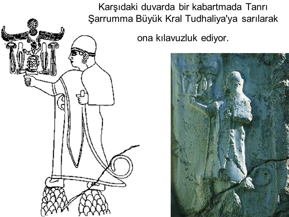 Karşıdaki duvarda bir kabartmada Tanrı Şarrumma Büyük Kral Tudhaliya'ya sarılarak ona kılavuzluk ediyor.