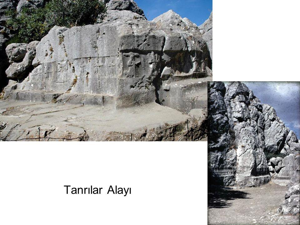 Karşıdaki duvarda bir kabartmada Tanrı Şarrumma Büyük Kral Tudhaliya ya sarılarak ona kılavuzluk ediyor.