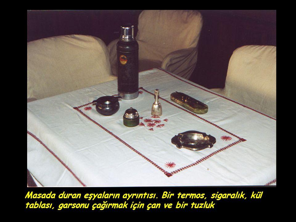 Masada duran eşyaların ayrıntısı. Bir termos, sigaralık, kül tablası, garsonu çağırmak için çan ve bir tuzluk