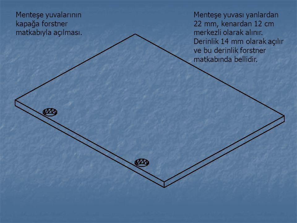 Menteşe yuvalarının kapağa forstner matkabıyla açılması. Menteşe yuvası yanlardan 22 mm, kenardan 12 cm merkezli olarak alınır. Derinlik 14 mm olarak