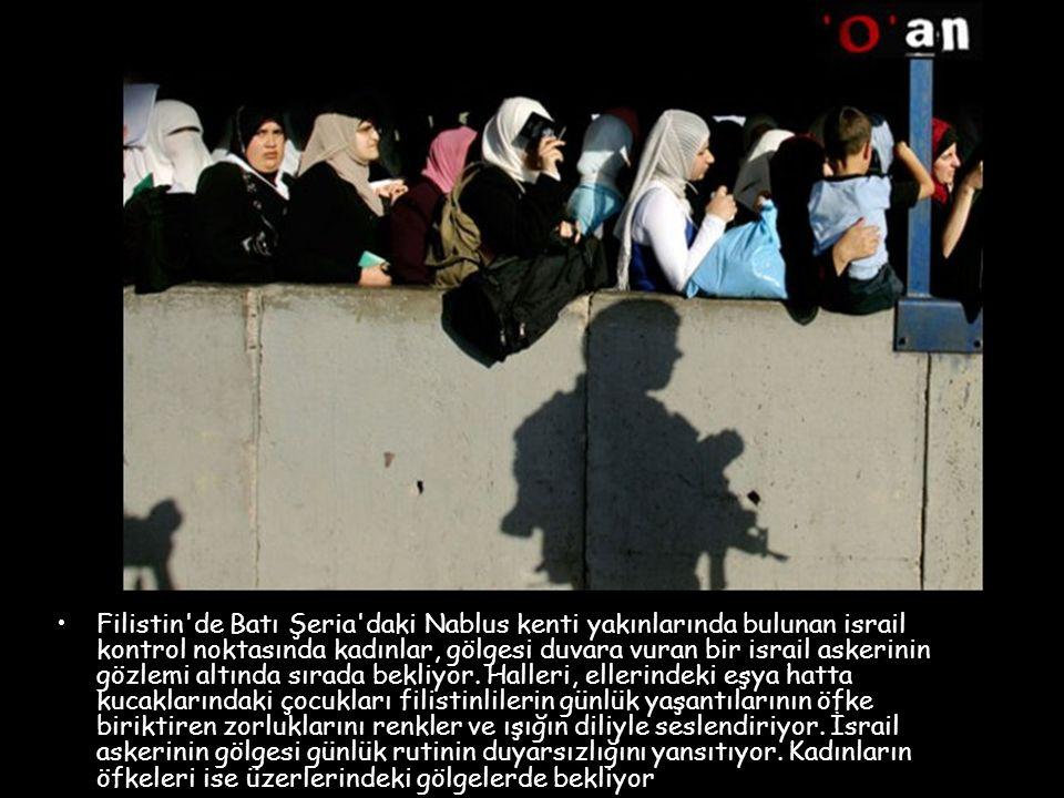 Filistin de Batı Şeria daki Nablus kenti yakınlarında bulunan israil kontrol noktasında kadınlar, gölgesi duvara vuran bir israil askerinin gözlemi altında sırada bekliyor.