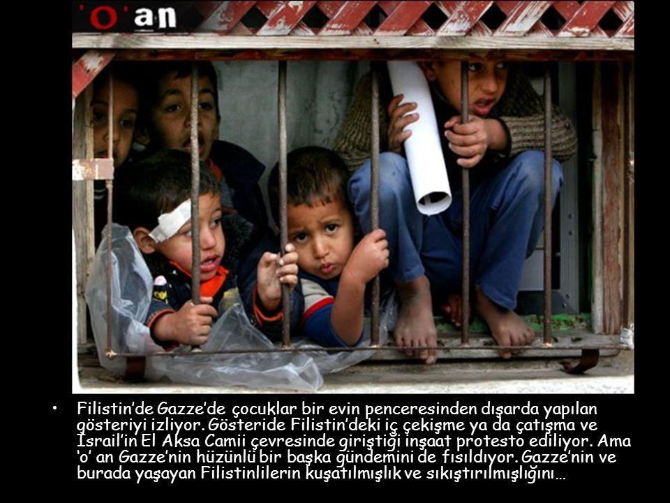 Filistin'de Gazze'de çocuklar bir evin penceresinden dışarda yapılan gösteriyi izliyor.