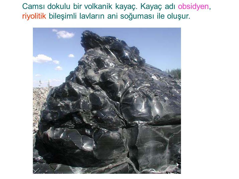 Camsı dokulu bir volkanik kayaç. Kayaç adı obsidyen, riyolitik bileşimli lavların ani soğuması ile oluşur.