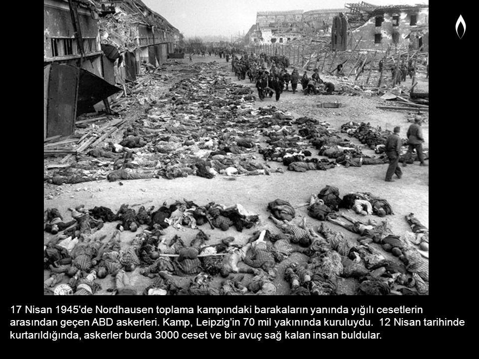 17 Nisan 1945'de Nordhausen toplama kampındaki barakaların yanında yığılı cesetlerin arasından geçen ABD askerleri. Kamp, Leipzig'in 70 mil yakınında