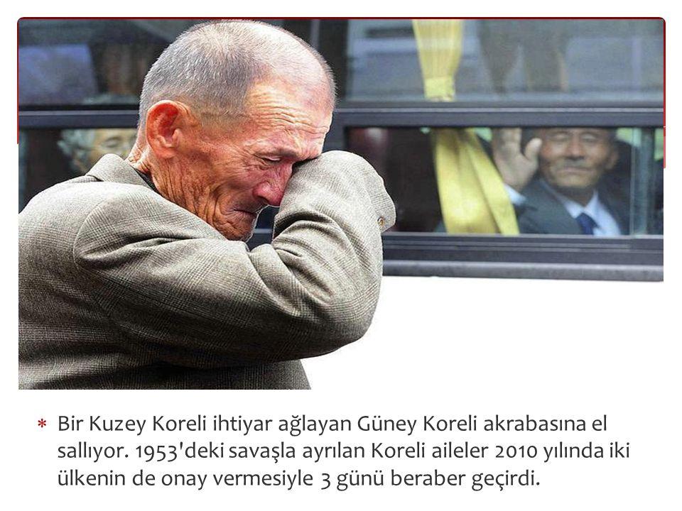  Bir Kuzey Koreli ihtiyar ağlayan Güney Koreli akrabasına el sallıyor.