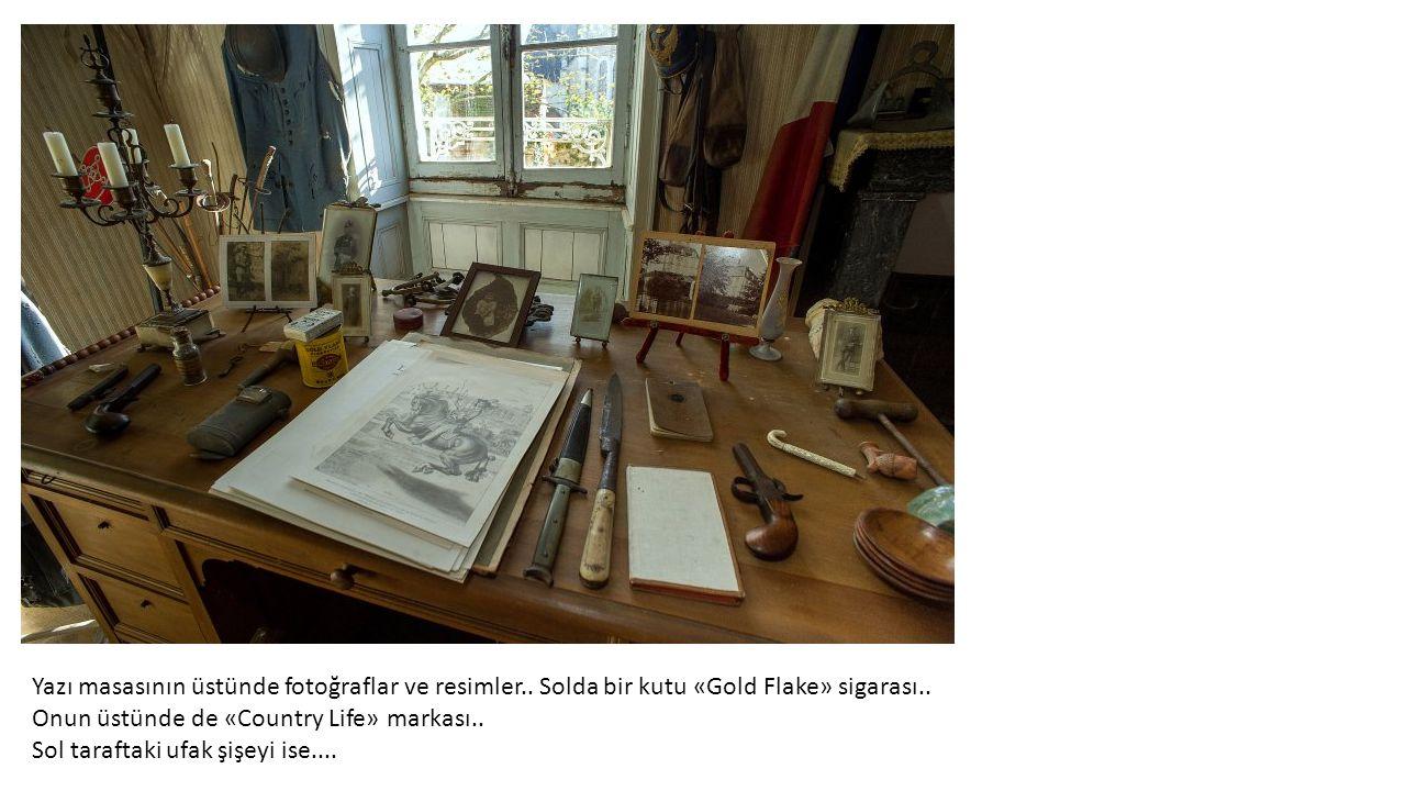 Yazı masasının üstünde fotoğraflar ve resimler..Solda bir kutu «Gold Flake» sigarası..