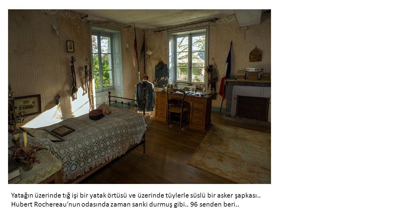 Yatağın üzerinde tığ işi bir yatak örtüsü ve üzerinde tüylerle süslü bir asker şapkası..