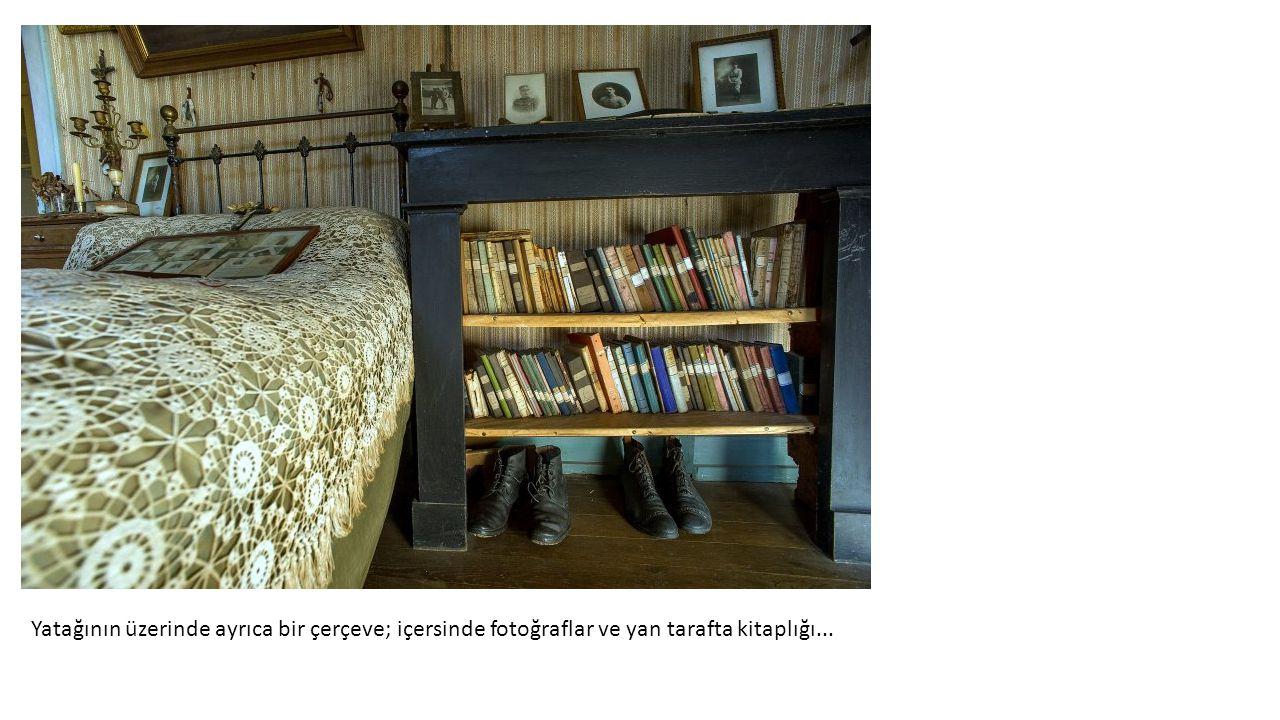 Yatağının üzerinde ayrıca bir çerçeve; içersinde fotoğraflar ve yan tarafta kitaplığı...