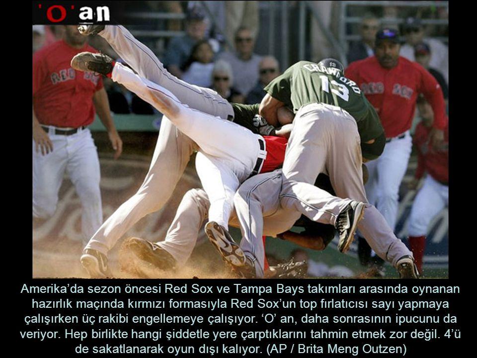 Amerika'da sezon öncesi Red Sox ve Tampa Bays takımları arasında oynanan hazırlık maçında kırmızı formasıyla Red Sox'un top fırlatıcısı sayı yapmaya çalışırken üç rakibi engellemeye çalışıyor.