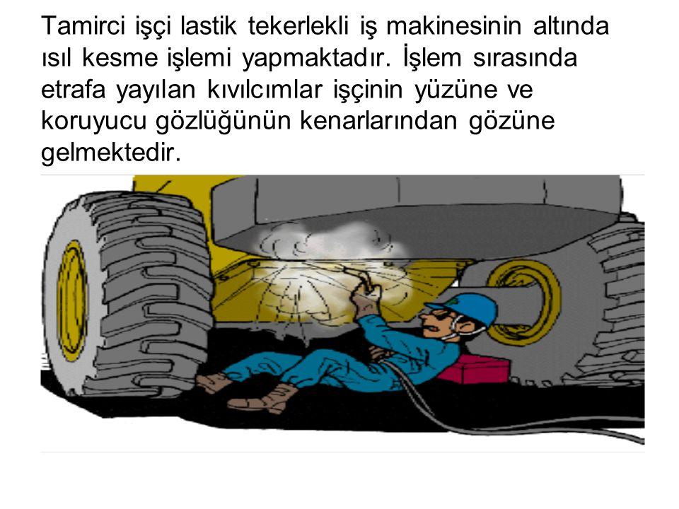 Tamirci işçi lastik tekerlekli iş makinesinin altında ısıl kesme işlemi yapmaktadır. İşlem sırasında etrafa yayılan kıvılcımlar işçinin yüzüne ve koru