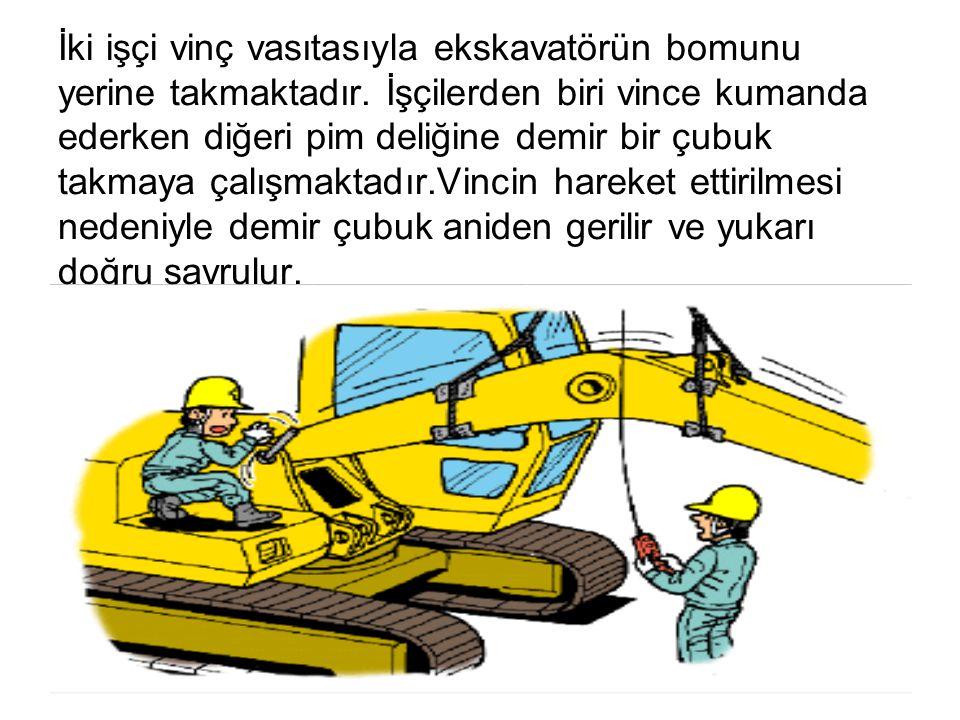 İki işçi vinç vasıtasıyla ekskavatörün bomunu yerine takmaktadır. İşçilerden biri vince kumanda ederken diğeri pim deliğine demir bir çubuk takmaya ça