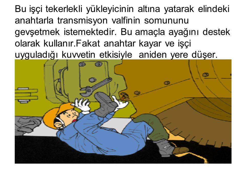 Bu işçi tekerlekli yükleyicinin altına yatarak elindeki anahtarla transmisyon valfinin somununu gevşetmek istemektedir. Bu amaçla ayağını destek olara