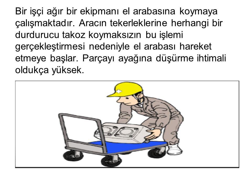 Bir işçi ağır bir ekipmanı el arabasına koymaya çalışmaktadır. Aracın tekerleklerine herhangi bir durdurucu takoz koymaksızın bu işlemi gerçekleştirme