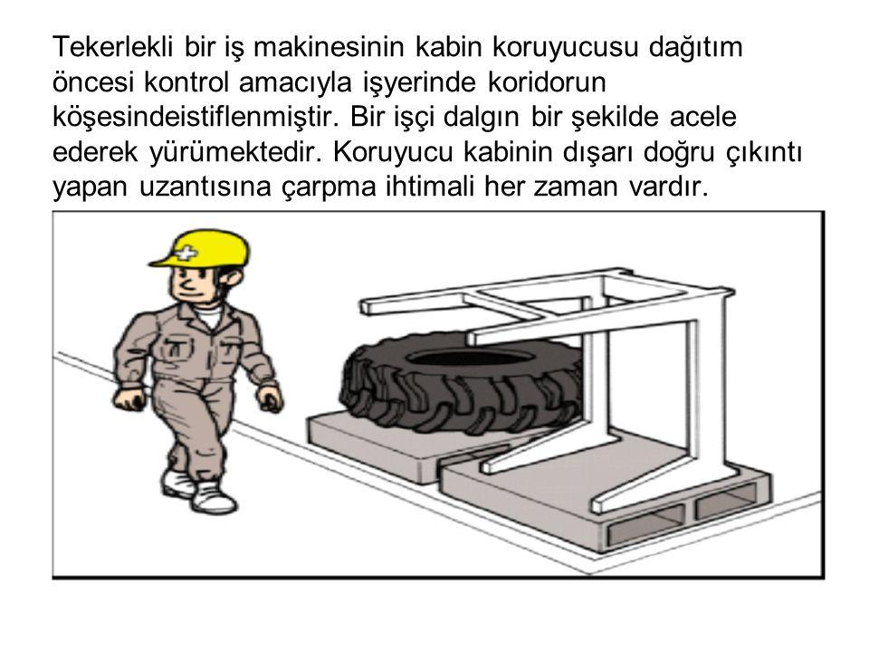Tekerlekli bir iş makinesinin kabin koruyucusu dağıtım öncesi kontrol amacıyla işyerinde koridorun köşesindeistiflenmiştir. Bir işçi dalgın bir şekild