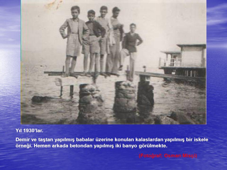 Yıl 1930'lar. Demir ve taştan yapılmış babalar üzerine konulan kalaslardan yapılmış bir iskele örneği. Hemen arkada betondan yapılmış iki banyo görülm