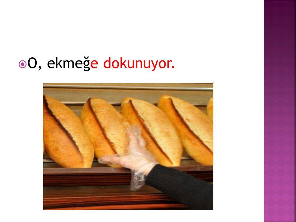  O, ekmeğe dokunuyor.
