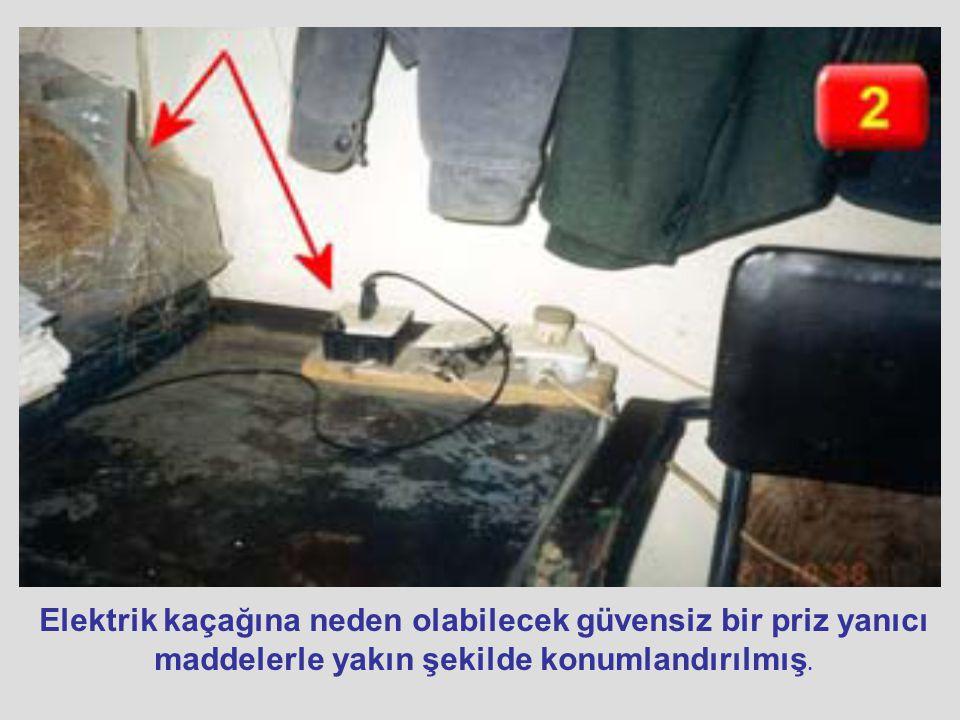 Elektrik kaçağına neden olabilecek güvensiz bir priz yanıcı maddelerle yakın şekilde konumlandırılmış.
