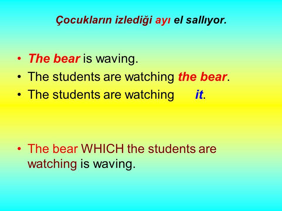Çocukların izlediği ayı el sallıyor. The bear is waving.