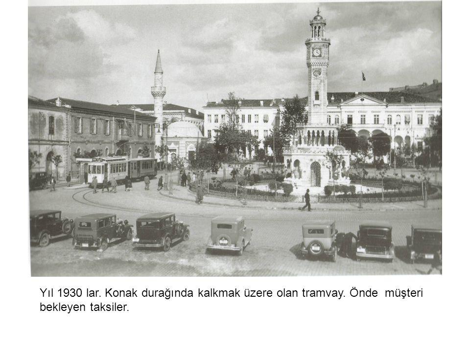 Yıl 1930 lar. Konak durağında kalkmak üzere olan tramvay. Önde müşteri bekleyen taksiler.