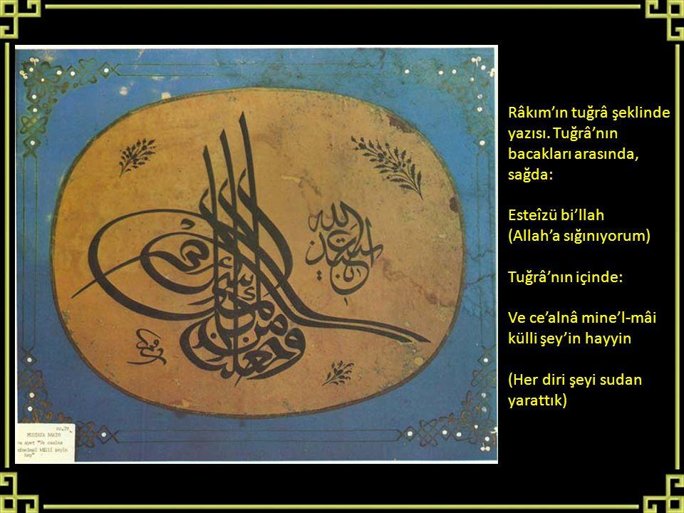 Râkım'ın tuğrâ şeklinde yazısı. Tuğrâ'nın bacakları arasında, sağda: Esteîzü bi'llah (Allah'a sığınıyorum) Tuğrâ'nın içinde: Ve ce'alnâ mine'l-mâi kül